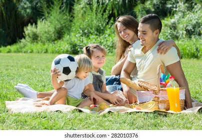 Young couple with little daughters having holiday with picnic