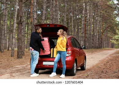 Young couple loading suitcases into car trunk on forest road