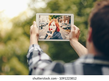 Young couple in a long distance relationship chatting over a video call, by using a tablet.