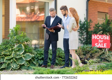Young couple looking for an apartment, showing agent which property they want to buy