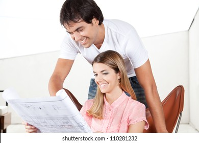 Young couple looking at blueprints at home.