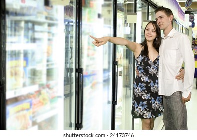 young couple looking at food near freezer in grocery store