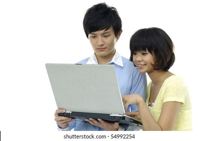 young couple looking into laptop on an isolated background