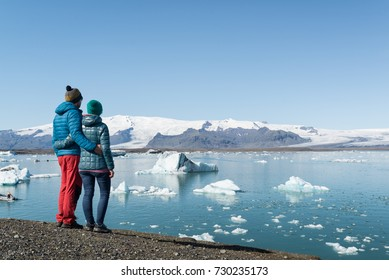 Young couple looking at Jokulsarlon glacier lake in Iceland