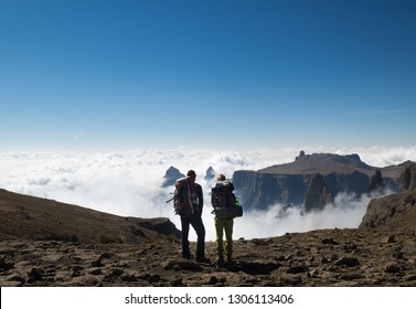 Young couple looking on the clouds below them from the top of the cliff in Dragon mountains in South Africa