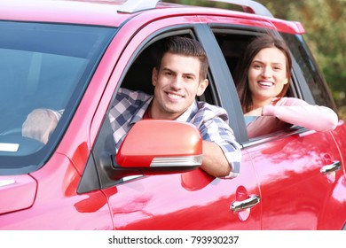Young couple looking out of new modern car