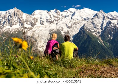 Young couple looking at panorama of Mont Blanc glacier from another hill, Chamonix, France, during famos trek - Tour du Mont Blanc