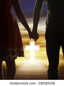 Young couple looking the shining cross. Religious concept