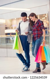 Young couple looking in shopping bags, checking shopping bags