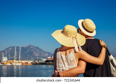 Young couple looks at the Alanya port surrounded by mountains