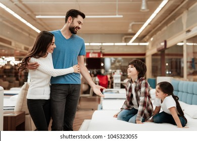 Young couple looks like children are sitting on mattress in furniture store. Happy family choosing mattresses in store. Orthopedic mattress, for comfortable sleep and healthy posture.