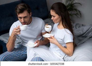 Young couple in loungewear drinking coffee in bed