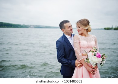 Young couple in love against lake. Girl with bouquet.