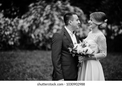 Young couple in love against spring bushes. Girl with bouquet.