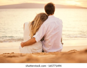 Young couple in love, Attractive man and woman enjoying romantic evening on the beach watching the sunset