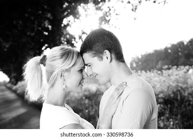 Young couple in love - beautiful sunset as a background, black and white