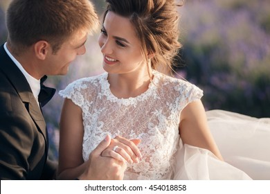 Young couple in love bride and groom, wedding day in summer. Enjoy a moment of happiness and love in a lavender field. Bride in a luxurious wedding dress.