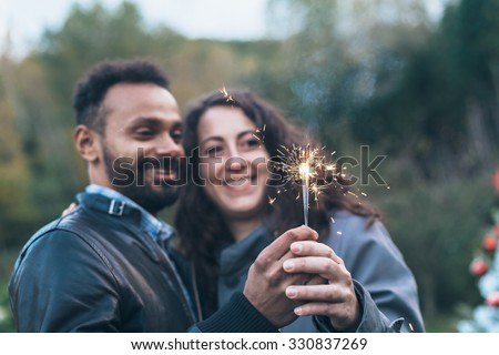 A young couple in love, celebrating an event, the New Year is coming, they are holding three lit sparkler. Detail on sparkler, behind them a forest and a Christmas tree