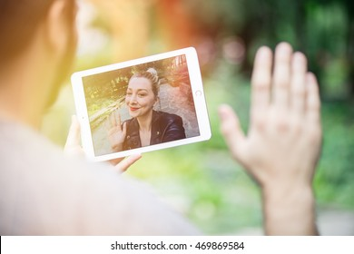 young couple in love chatting over a video call, by using a tablet. graded with a flare