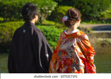 Young couple in love with colorful Japanese clothing on a sunny day in a garden in Tokyo, Japan