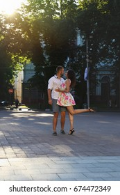 Young couple in love dancing on the street. Beautiful girl with long hair walking with her beloved. Stylish couple dancing on the sunny street in Lviv, Ukraine