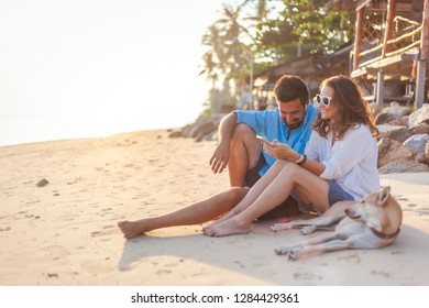 Young couple in love with a dog sitting on the sandy seashore in the rays of the sunset, vacation travel honeymoon in the tropics