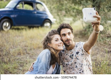 Young couple in love doing a picnic outdoors in Tuscany wine country and taking a selfie with an instant camera
