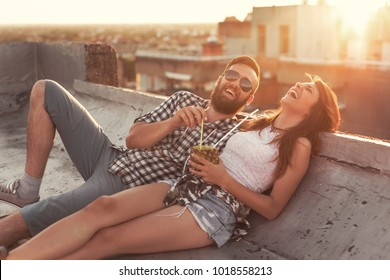 Young couple in love drinking a pineapple cocktail and having fun at rooftop party in sunset. Focus on the guy