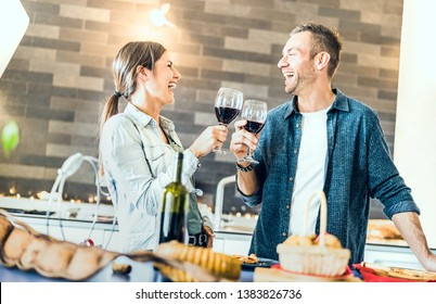 Young couple in love drinking red wine in house kitchen - Happy millenial people at home enjoying aperitif time cheering together at jubilee anniversary - Genuine youth concept on bright indoor filter