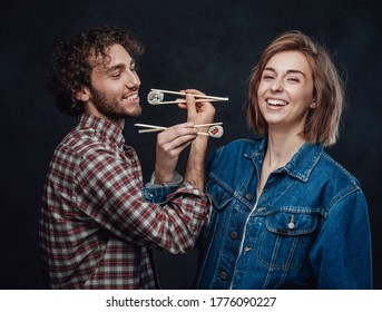 Young couple in love eat sushi on bruderschaft, enjoys and having fun together. Studio photo