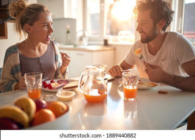 Ein junges Ehepaar liebt das Frühstück zu Hause an einem schönen sonnigen Morgen. Beziehung, Liebe, zusammen, Frühstück