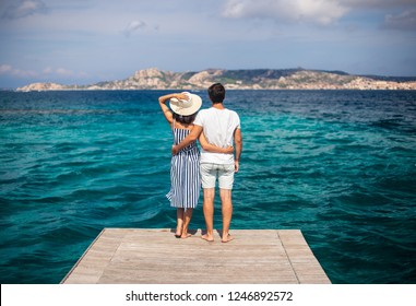 Young couple in love enjoy beautiful sea landscape on pier in Italy. honeymoon, romantic concept