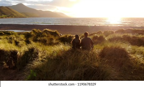 Young couple in love enjoy the sunset over the ocean