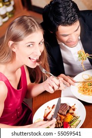 Young couple in love is enjoying a romantic dinner, he has some noodles while she is eating a good steak