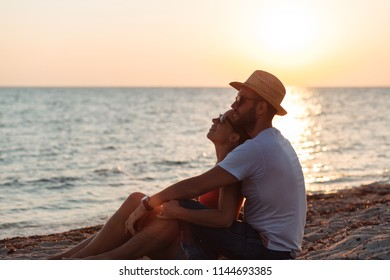 Young couple in love enjoying sunset on the beach