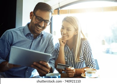 Young couple in love enjoying time spending with each other in café and shopping online.
