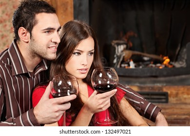 Young couple in love enjoying wine near fireplace