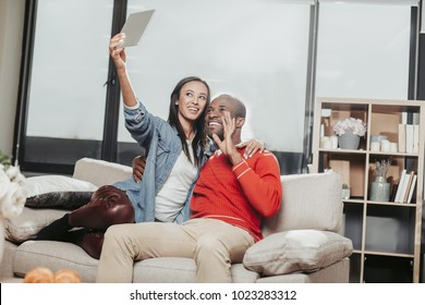 Young couple in love expressing enjoyment while resting inside and making selfie with tablet. Copy space in right side