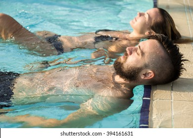 Young couple in love floating on the edge of a swimming pool, sunbathing
