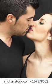 Young couple in love giving himself a kiss on black background