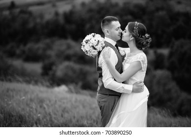 Young couple in love, groom and bride in wedding dress at the nature. Newlyweds hold hands and look at each other. Wedding. Wedding day. Bridal bouquet.