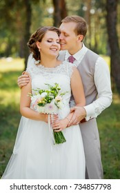 Young couple in love, groom and bride in wedding dress at the nature. Wedding. Wedding day. Bridal bouquet.