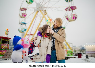 Young couple in love with a happy young man with a beard and a woman on a background of a fucking colossus, a Ferris wheel resting, a date in an amusement park in the winter in the Christmas holidays.