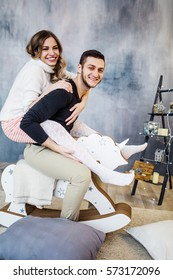 Young couple in love have fun with toy horse on new years eve