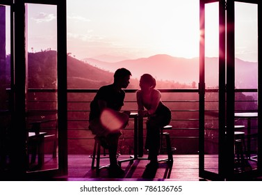 young couple in love and have fun on valentine day. mountain on background. windows or door on foreground. processed in pink tone. silhouette shot. shot at balcony. lens flare is purposely.