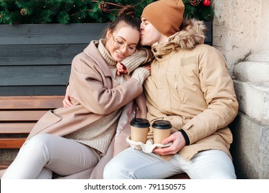 Young couple in love have fun outdoor in winter and drinking coffee together sitting on the bench