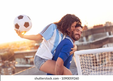 Young couple in love having fun on a building rooftop after playing football. Guy giving a piggyback ride to his girlfriend