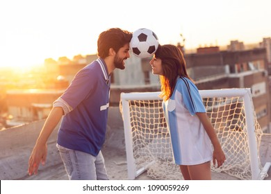 Young couple in love having fun on a building rooftop after playing football, dancing and balancing with the ball between their heads