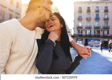 Young couple in love having fun while enjoying their spring vacation in Barcelona city. Beautiful wife and husband sped honeymoon in Europe. Attractive female laughing during dating with boyfriend