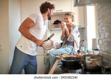 A young couple in love having good time while preparing a breakfast together on a beautiful morning. Cooking, together, kitchen, relationship - Shutterstock ID 1905382240